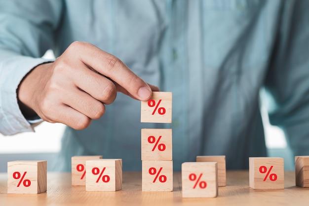 Verkoopvolume of marketingcapaciteit vergroten, zakenman stapelt houten blokjesblok dat schermpercentage afdrukt.