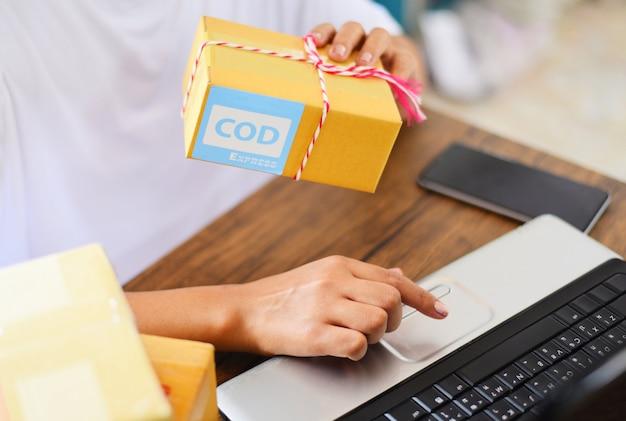 Verkopen van online e-commerce verzending online winkelen levering en bestellen opstarten van klein bedrijfseigenaar werken concept - vrouw verpakking kartonnen doos pakketbezorging aan klant contant bij aflevering express