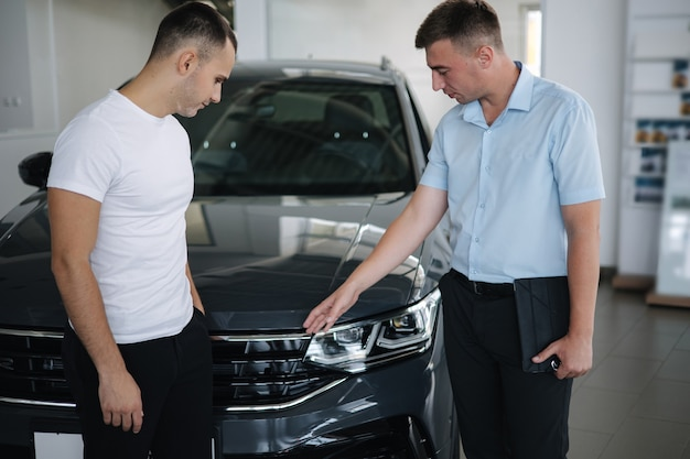 Verkoper die auto's verkoopt bij autodealer man die auto kiest in autoshowroom
