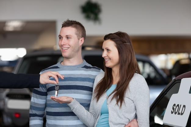 Verkoper die autosleutels geeft aan een vrouw