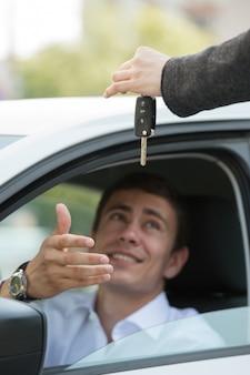 Verkoper die de zakenman van de sleutelsauto overhandigt