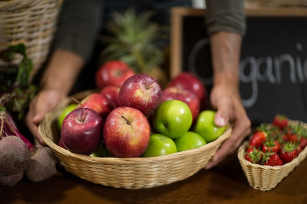 Verkoper die een mand van appelen houdt bij de kruidenierswinkel