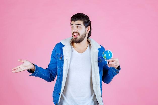 Verkoper die een mini-wereldbol vasthoudt en het product promoot