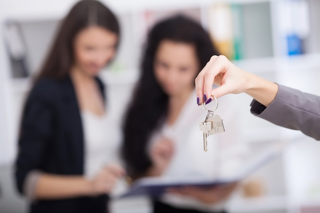 Verkoper die een modelhuis in de hand draagt, levert de huissleutel aan de koper, klanten ontvangen huissleutels van verkoop aan huis, leveren huissleutels tussen verkoper en koper.