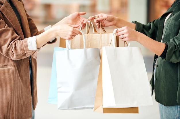 Verkoper die papieren zakken met verpakte goederen aan de vrouw geeft en haar bedankt voor het winkelen