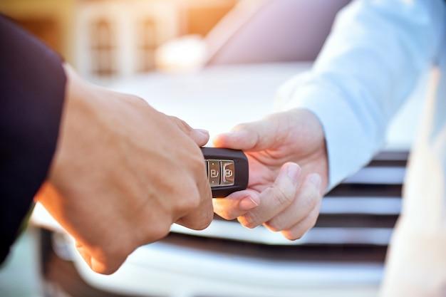 Verkoper die zeer belangrijke auto geven aan klant, het concept van de autoverkoop