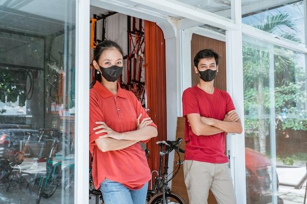 Verkoper en verkoopster met masker staan met gevouwen handen voor de glazen deur te leunen