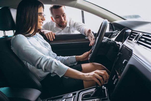 Verkoper en vrouw die een auto in een autotoonzaal zoeken