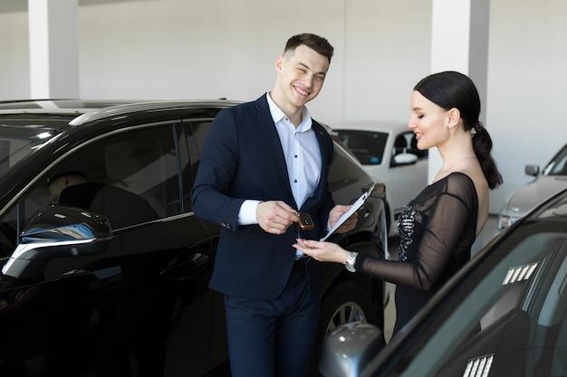 Verkoper geeft de koper de sleutels van een nieuwe auto in de showroom
