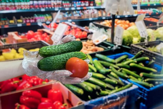 Verkoper in handschoenen verkoopt verse groenten. man geeft dollars voor boodschappen in de supermarkt. covid19