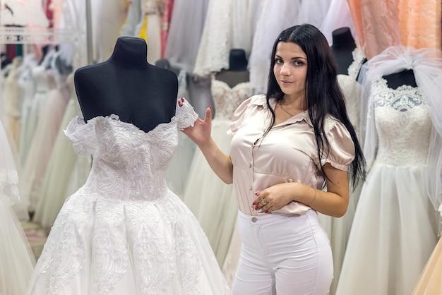 Verkoper in huwelijkssalon jurken voor bruid demonstreren