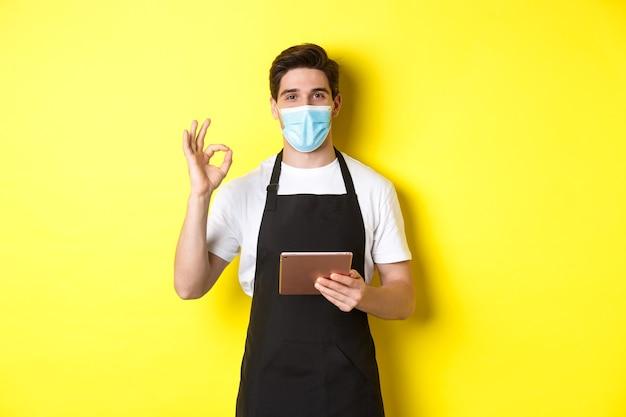 Verkoper in medisch masker en zwarte schort die ok teken tonen, orden met digitale tablet, gele muur aanneemt