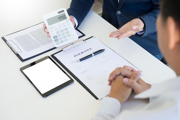 Verkoper met een sleutel en het berekenen van een prijs bij het dealerbedrijf