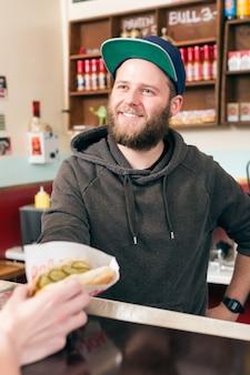 Verkoper met hotdog in fast food snackbar