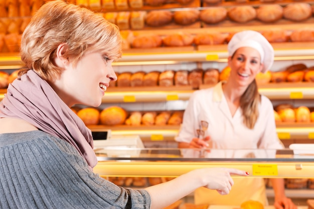 Verkoper met vrouwelijke klant in bakkerij