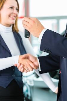 Verkoper of autoverkoper en klant bij dealer, ze schudden elkaar de hand, overhandigen de autosleutels en bezegelen de aankoop van de auto of nieuwe auto