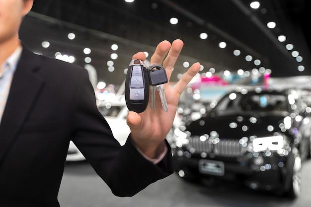 Verkoper of handelaar die autosleutels aanbieden aan nieuwe eigenaar in showroom, koop of huurconcept.
