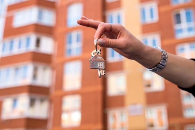 Verkoper overhandigen sleutels op de achtergrond van de woonwijk. verkoop of huur concept