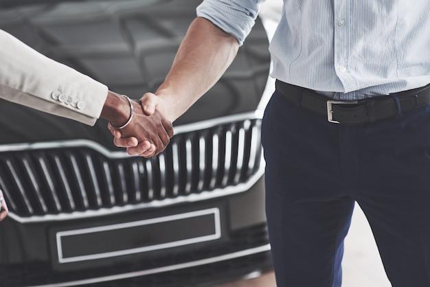 Verkoper shakeshands met mannelijke afrikaanse klant na verkoop van een nieuwe auto.