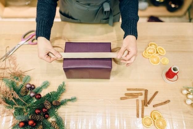 Verkoper siert geschenkdoos met gouden lint