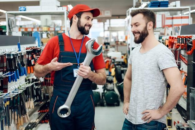 Verkoper toont nieuwe gigantische sleutel aan klant