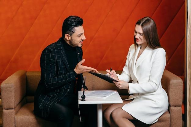 Verkopers laten de mannelijke klanten het bedrijfsconcept van het verkoopcontract en de ondertekening van het contract ondertekenen