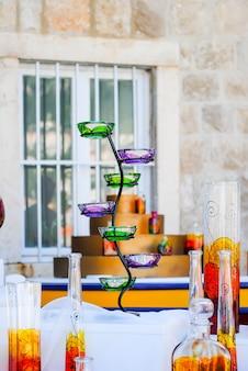 Verkopers verkopen op de stadsmarkt een verscheidenheid aan glasproducten, geschilderd in verschillende kleuren.