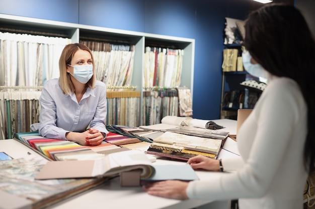 Verkopersadviseur communiceert met de klant die een beschermend medisch masker draagt en veilig is