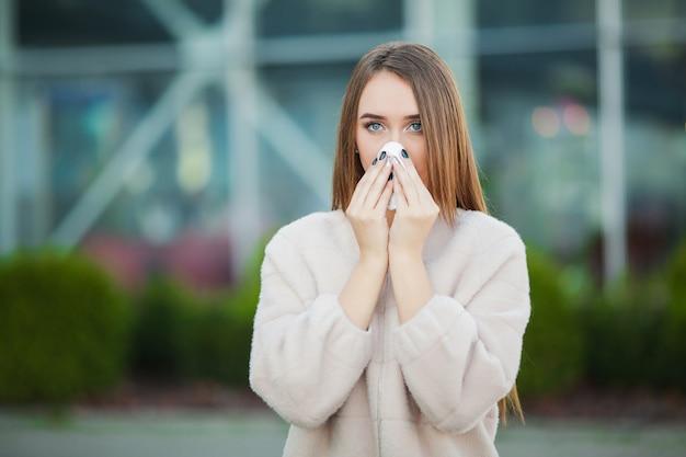 Verkoudheid en griep. jong aantrekkelijk meisje, verkouden op straat, veegt haar neus af met een servet