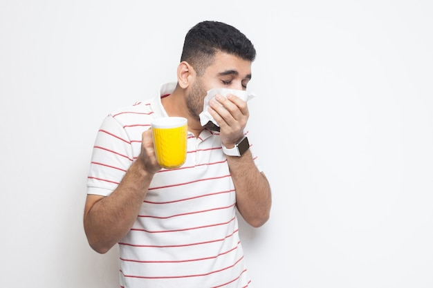Verkoudheid en griep. portret van een zieke, bebaarde jongeman in gestreept t-shirt die staat, weefsel vasthoudt, zijn neus schoonmaakt, warme drank vasthoudt, probeert te worden behandeld. indoor studio opname, geïsoleerd op een witte achtergrond.