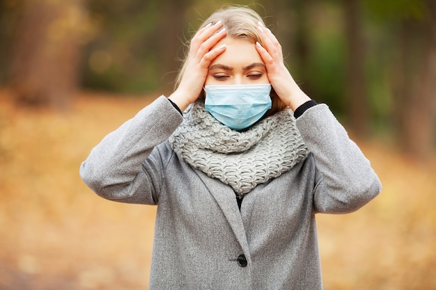Verkoudheid en griep. vrouw met een medisch gezichtsmasker bij openlucht
