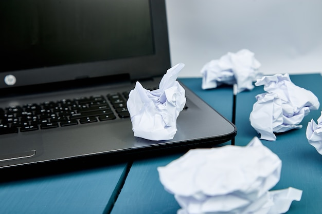 Verkruimelde papieren op de werkplek met een laptop