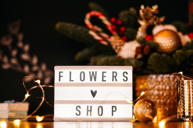 Verlaagt het uithangbord van de winkel en de kerstverlichting over een onscherpe dennenboomregeling.