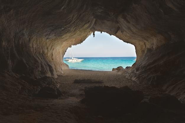 Verlaat de grote grot naar het strandzand en de blauwe zee, uitzicht van binnenuit. mediterrane kust, sardinië, italië.