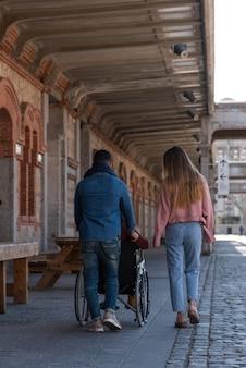 Verlamde jonge man in een rolstoel, vergezeld van een jonge man en een meisje dat wandelt
