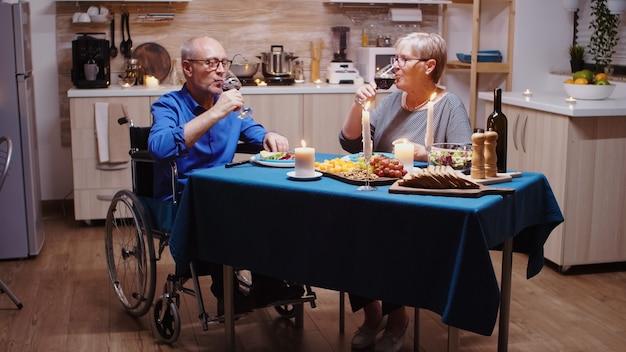 Verlamde man roosteren met wijn met zijn vrouw. senior oude man in rolstoel dineren met bejaarde vrouw zitten in de keuken. geïmobiliseerde verlamde gehandicapte bejaarde echtgenoot die romantisch diner heeft