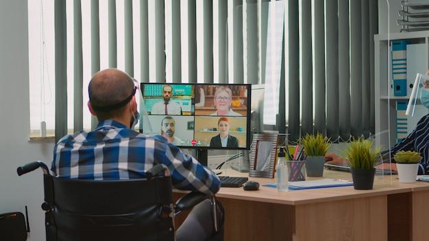 Verlamde manager in rolstoel die met masker en vizier spreekt tijdens videogesprek met online conferentie in bedrijfsbureau. geïmmobiliseerde freelancer die werkt in een financieel bedrijf met respect voor sociale afstand