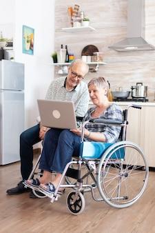 Verlamde senior vrouw in rolstoel en man browsen op internet met behulp van laptop in de keuken. gehandicapte gehandicapte oude bejaarde die moderne communicatietechnologie gebruikt.