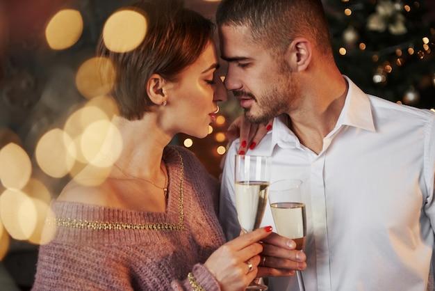 Verlangen hangt in de lucht. mooi paar dat nieuw jaar binnenshuis viert met klassieke mooie kleren aan