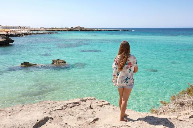 Verlangen naar de zomer, verlangen naar vakantie. achteraanzicht op vrouwelijke toerist die geniet van het kristalheldere water van de oceaan.
