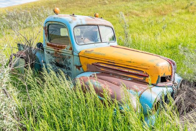 Verlaten antieke blauwe en gele vrachtwagen in hoog gras