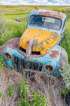 Verlaten antieke blauwe en gele vrachtwagen