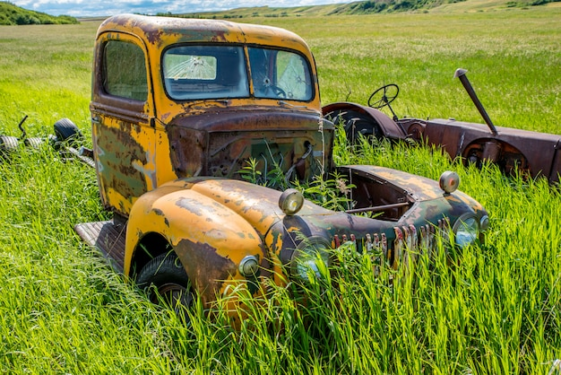 Verlaten antieke gele vrachtwagen en trekker in hoog gras