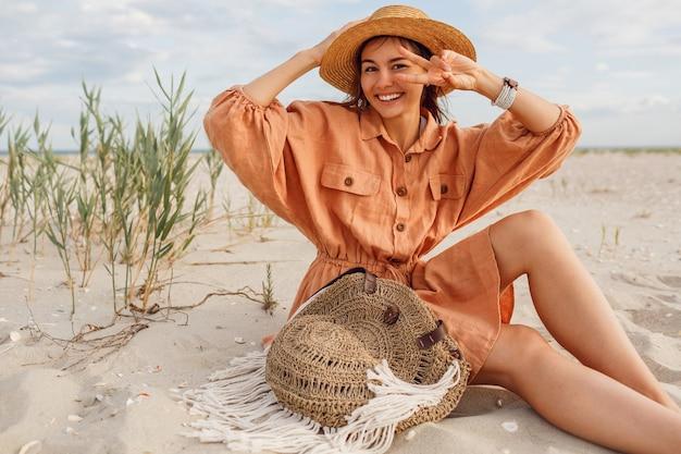 Verlaten brunette vrouw met perfecte glimlach plezier op zonnig strand, zittend op wit zand in de buurt van de oceaan.