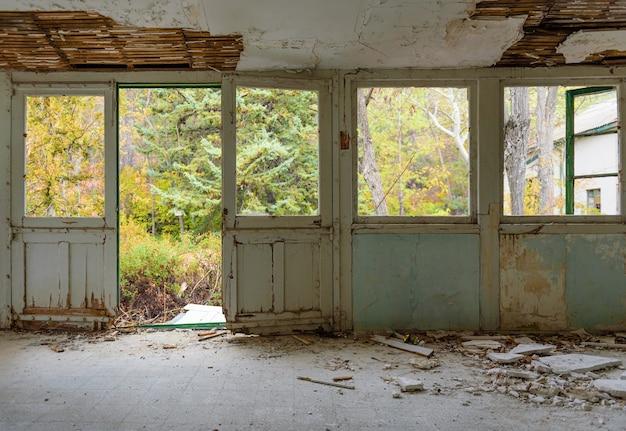 Verlaten huisbinnenland. galerij met deur- en raamkozijnen, gebroken glas en gevallen gips, overwoekerde herfsttuin gezien door de ramen the
