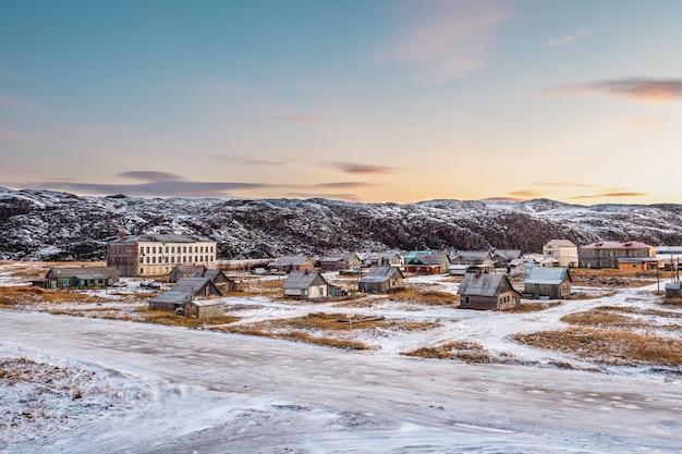Verlaten huizen tegen de arctische hemel. oud authentiek dorpje teriberka. kola-schiereiland. rusland.
