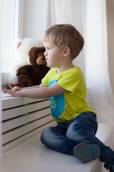 Verlaten kind. eenzame kleine jongen zit bij het raam in een weeshuis