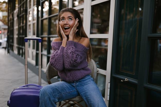 Verlaten model met de blauwe koffer zittend op de stoel bij het café, in de paarse trui, jeans, make-up, kapsel, emoties, herfst, blond, gelukkig, gebreid, glimlachend