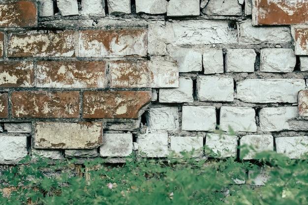 Verlaten oude muur van geruïneerde rode en witte bakstenen. achtergrondafbeelding, kopieer ruimte