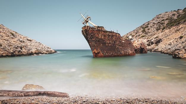 Verlaten roestig schip in de zee in de buurt van enorme rotsformaties onder de heldere hemel